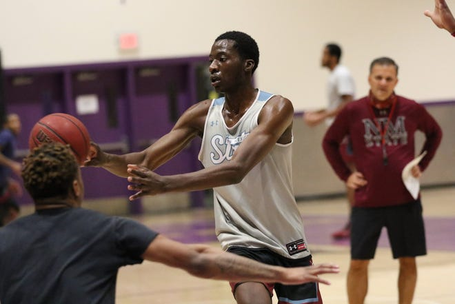 Redshirt junior Wilfried Likayi passes the ball during a New Mexico State practice on the campus of Grand Canyon University.