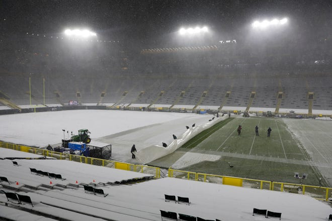 Workers get the field at Lambeau Field ready as it snows before Sunday night's game.