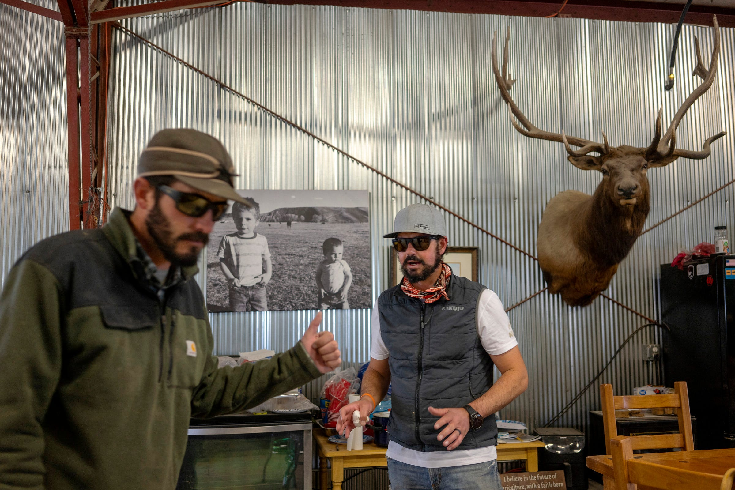 Doug Bruchez, left, talks with his brother Paul Bruchez, right, while they fix a door in the shop where they keep their tractor and ranch equipment near Kremmling, Colorado.