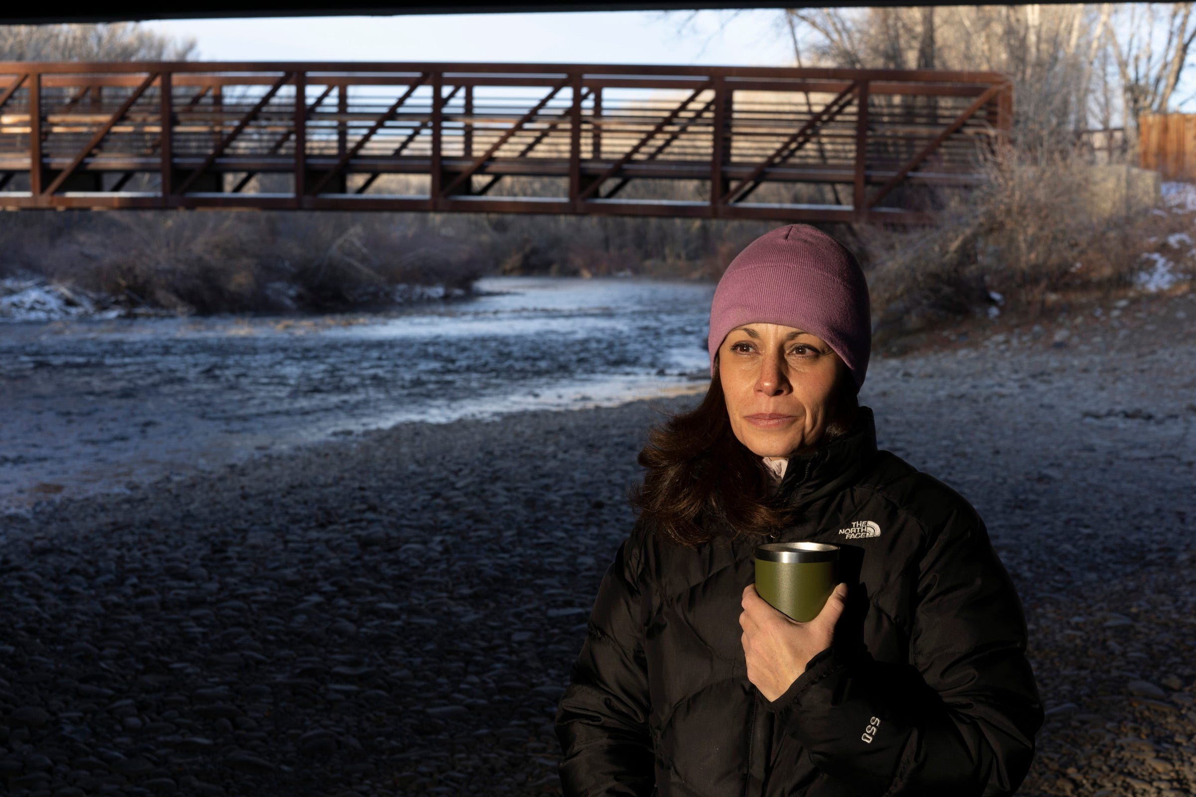 Sonja Chavez, general manager of the Upper Gunnison River Water Conservancy District, stands on the banks of the Gunnison River, a tributary of the Colorado River. The river's flow has declined dramatically over the past year.