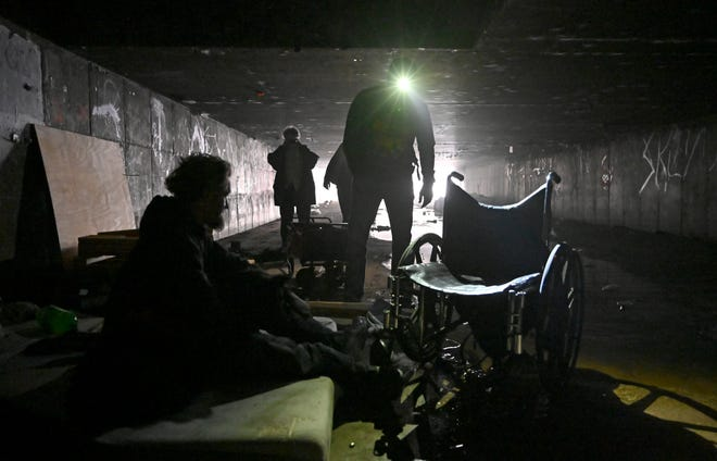 FILE - In this Dec. 5, 2020, file photo, a man who identified himself as Wheeler, left, speaks with Dave Marlon of CrossRoads of Southern Nevada, during an outreach in the underground tunnels to offer counseling, food and water to the homeless living beneath the city in Las Vegas. When census takers tried to count the nation's homeless population, they ran into many problems that could threaten the accuracy of the effort. That's what a half dozen census takers around the U.S. tell The Associated Press.