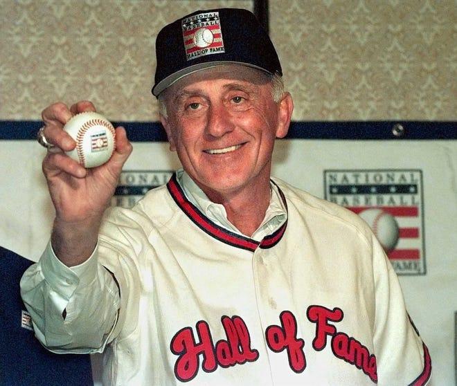 Phil Niekro montre sa prise de knuckleball lors d'une conférence de presse après avoir été élu au Temple de la renommée du baseball.