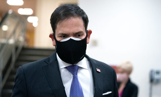 Sen. Marco Rubio, R-Fla., wears a protective mask while walking in the U.S. Capitol in Washington, Dec. 11, 2020.