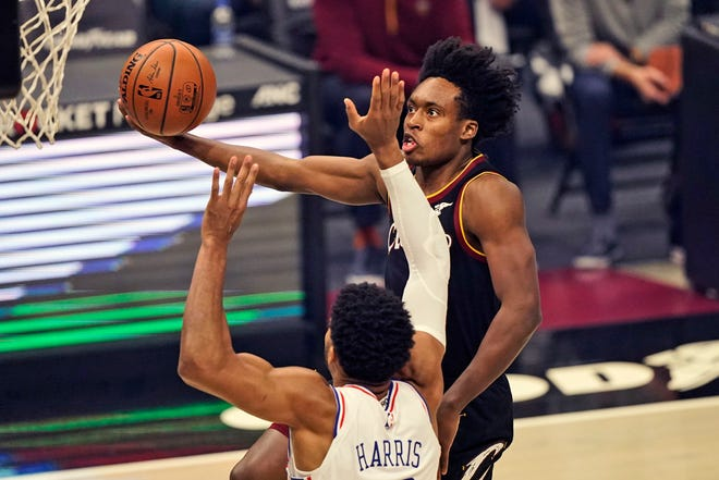 Cavaliers guard Collin Sexton, right, drives to the basket against Philadelphia 76ers' Tobias Harris in the first half of the Cavs' 118-94 win Sunday night at Rocket Mortgage FieldHouse. [Tony Dejak/Associated Press]
