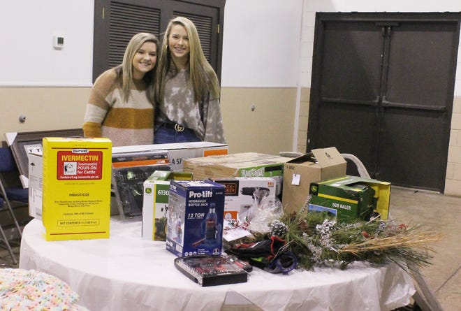 Two junior cattlemen association members pose with some of the items donated for the auction the association held recently to raise funds for their annual scholarships. Pictured are (from left) Malana Moore and Leslie Barber.