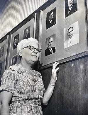 Emma Fuller, longtime Augusta mayoral secretary, poses in 1962 with photos of some of those she served.