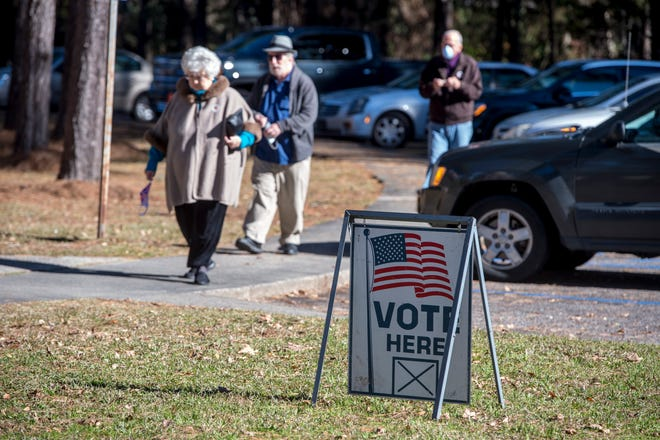 Voters make their way to the polls at the Warren Road Community Center in Augusta, Ga., Monday morning December 28, 2020.