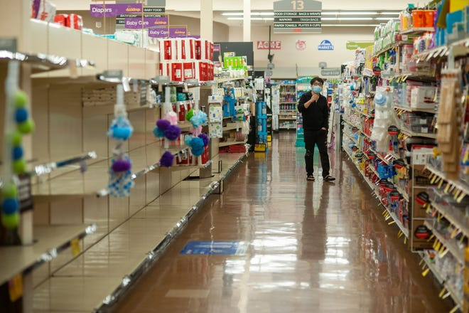 File - A man walks down an aisle while shopping as employees and customers follow safety protocols to help avoid coronavirus Tuesday, April 14, 2020 at ACME Market in Doylestown, Pennsylvania.