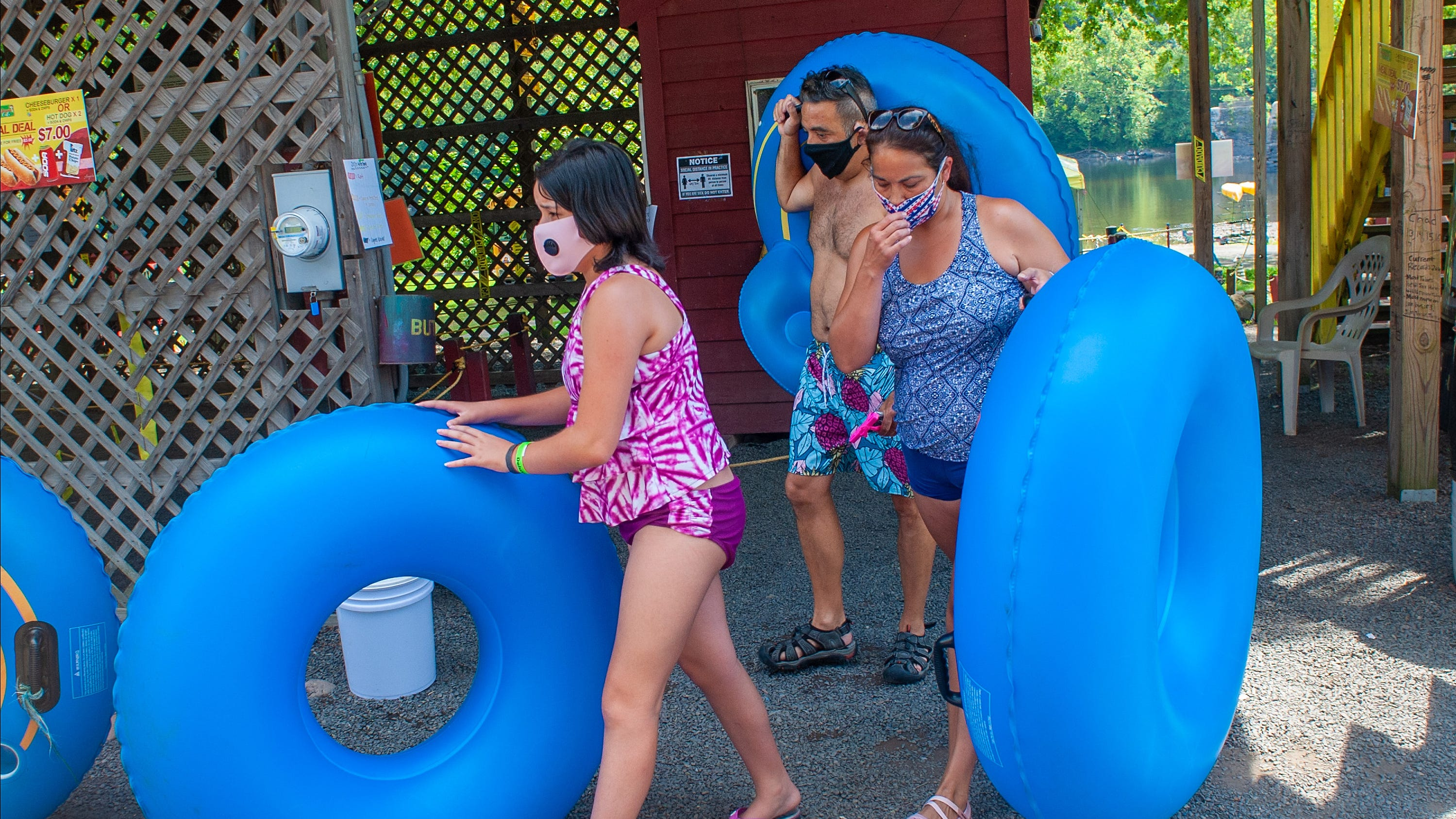 From left, Katie Caliguire, her dad Vince Caliguire and mom Chrissy Caliguire of Delanco, New Jersey carry their tubes to the bus during a day of tubing on the Delaware River Thursday, July 30, 2020 at Bucks County River Country in Point Pleasant, Pennsylvania. Usually opening in May, Bucks County River Country didn't open until June due to COVID-19 concerns. Since they opened for the season the weather has been consistently in the 90's and they have been very busy, having one of their best weekends ever only a few weeks ago.