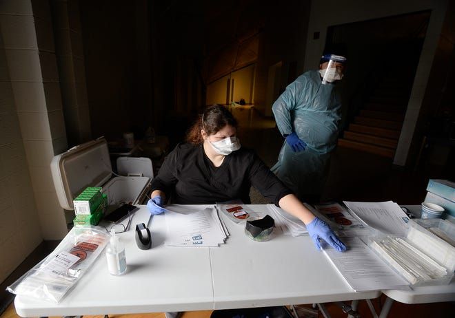 Ashley Harmer, an employee from Aspen Medical International, processes COVID-19 paperwork last year from inside the Golden Dome at the Community College of Beaver County. AMI is contracted by the Department of Health.