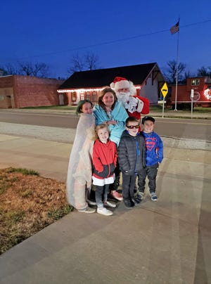 Santa poses with Evelyn Arnold, Alan Arnold, Rawhi Alabidi, Fatimah Alabidi, and Riley Arnold on Dec. 23 after passing out candy to children in Bunceton. He then headed back to the North Pole.