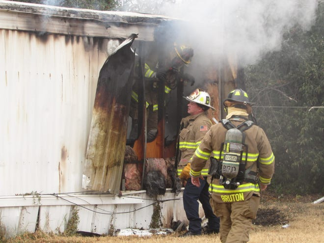Assistant Brownwood Fire Chief Jody Horton and firefighter Brent Bruton are picture outside a mobile home heavily damaged by a fire in the 3300 block of Stephen F. Austin Monday morning.