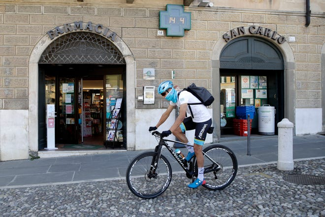 """Italian professional cyclist Davide Martinelli rides his bike after collecting medicine at a pharmacy to be delivered to residents last April. """"I've got a bike and two legs in pretty good form,"""" he said."""