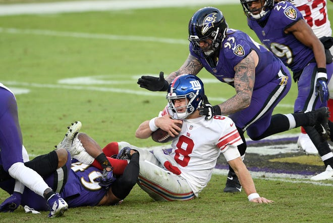 New York Giants quarterback Daniel Jones is sacked by Baltimore Ravens linebacker Chris Board, left, as defensive end Derek Wolfe (95) helps bring him down Sunday in Baltimore.
