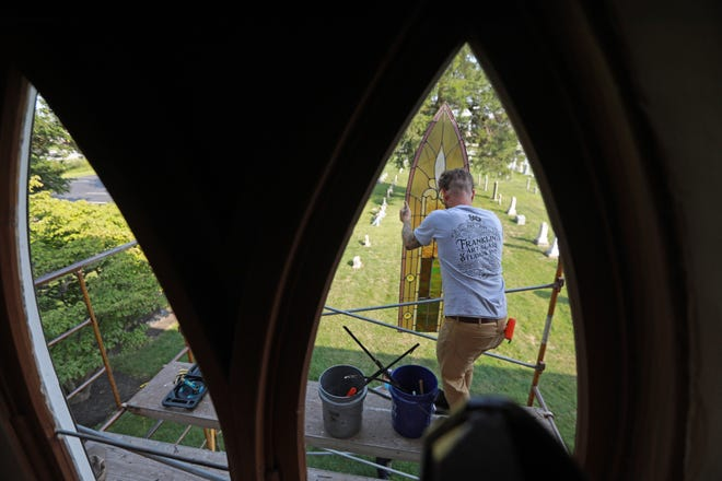 William Holterman lowers a piece of stained glass from St. James Lutheran Church to his co-worker Tim Albon. They spent nearly a week removing the windows in preparation for restoration work at Franklin Art Glass in German Village.