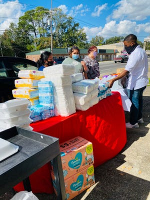 Volunteers distribute items at a recent Lifted by Love fundraiser.
