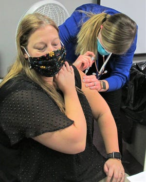 Pomerene Hospital nurse Tammy Gutheridge gets her COVID-19 vaccination, administered by Holmes County Health District nurse Courtney Struble Monday in the Holmes County General Health District meeting room.