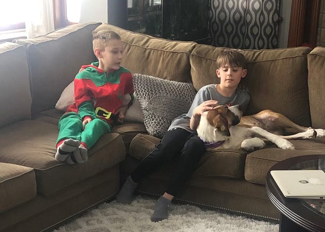 Caleb Lega and Blake Marshall enjoy their new family dog Emma, who they fostered over Christmas from the Wayne County Dog Shelter.