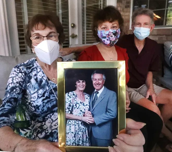 Judy Ronci (at left) holds a photo of her late husband, Sal Ronci, alongside her daughter Julie Sipes and son-in-law Ken Sipes. Sal Ronci, a longtime music educator and well-known band leader in Daytona Beach, died of coronavirus on Nov. 9. He was 83.