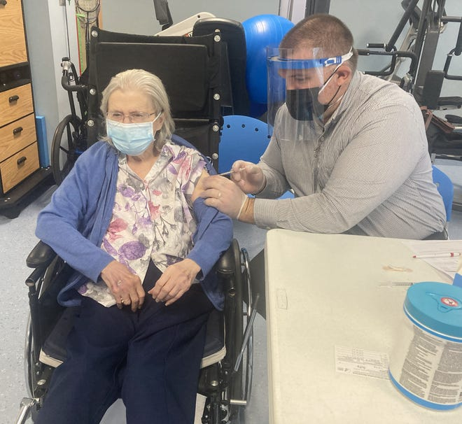 Resident Delphina Robaskiewicz, 89, gets a first dose of the Pfizer COVID-19 vaccine from Walgreens' Nathan Radicella at LECOM Senior Living on Monday. [VALERIE MYERS/ERIE TIMES-NEWS]