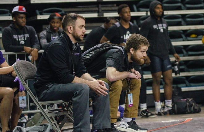 Waldorf University interim head coach Maurie Tomke (seated, left) coaches in the NJCAA National Wrestling Championships last year.