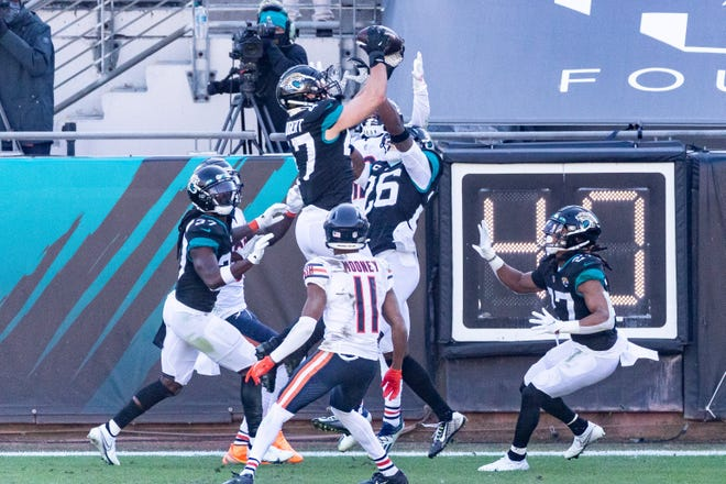 Jaguars linebacker Joe Schobert (47) leaps high for a second-quarter interception on Sunday against the Bears.