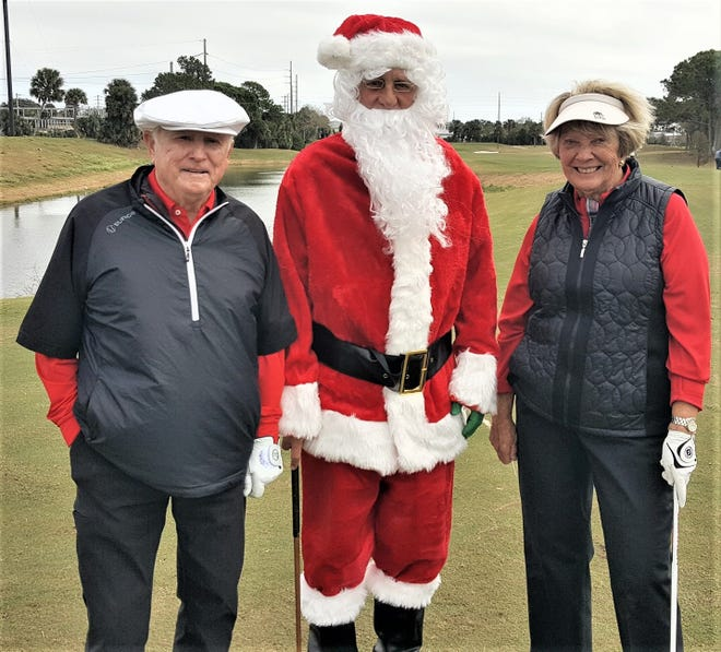 Santa Claus discusses tournament strategy with PGA Tour Commissioner Deane Beman and his wife, Judy, on the first tee during the JAGA Family Championship.