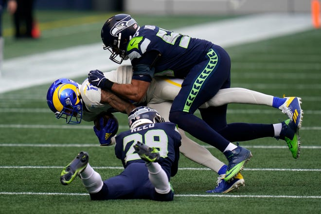 Los Angeles Rams wide receiver Josh Reynolds (11) is tackled by Seattle Seahawks free safety D.J. Reed (29) and linebacker K.J. Wright (50) during the first half of Sunday's game in Seattle.
