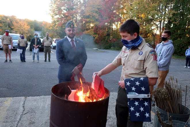 In this Oct. 13 photo, Jondavid Longo, Republican mayor of Slippery Rock, Pa., center, presides over a Boy Scouts flag retirement ceremony where worn-out flags are cut up and burned in Slippery Rock. Longo says the 2020 election has changed politics in his town, surfacing resentments from voters on both sides. The lingering tensions now overshadow issues once considered local, such as funding police and libraries. (AP Photo/Ted Shaffrey)