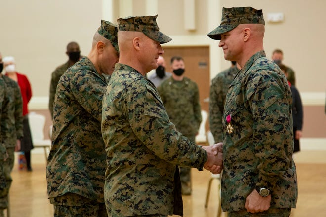 U.S. Marine Corps Maj. Gen. Julian D. Alford, left, commanding general, Marine Corps Installations East-Marine Corps Base Camp Lejeune, awards Sgt. Maj. Charles A. Metzger, right, outgoing sergeant major for MCIEAST-MCB Camp Lejeune, the Legion of Merit during a relief and appointment ceremony on Camp Lejeune, Dec. 21.