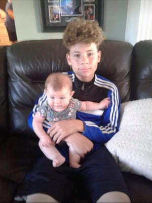 In this 2017 photo, Elijah Mayhew of Florida holds cousin Ensley. Months later, Mayhew, 15, died of a gunshot wound. His sister Kaybriel Mayhew, 21, of Illinois  had his ashes in her car when it was stolen last week. So far, there has been no sign of the car or ashes.