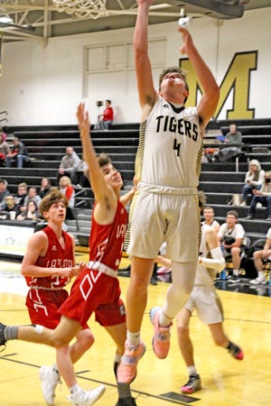 Marceline High School Tiger Will Heller gets inside for an easy lay-in and two of his game-high 19 points during the third period of the MHS' boys Dec. 18 rout of visiting La Plata. The Tigers and Lady Tigers are slated to visit Hallsville Saturday afternoon.