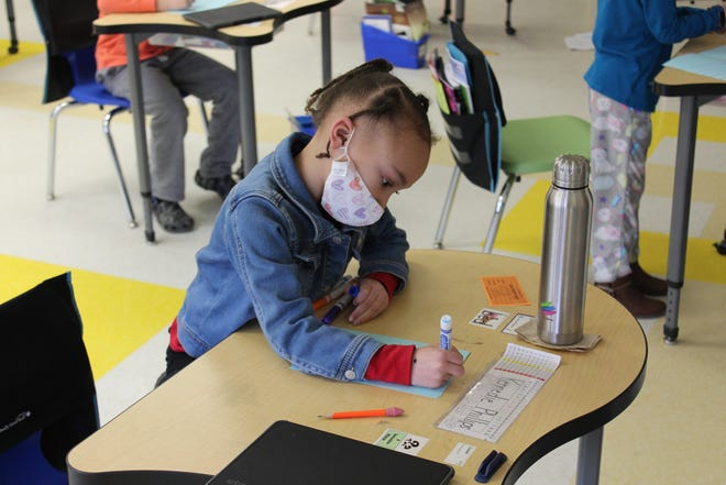 A student at T.J. Connor Elementary School makes a thank-you card for an essential worker.