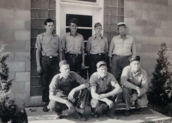 Sam Martin is back row, far right. Lewis Martin, Sr. is front row, far right. Behind them is the original front entrance of the Roanoke store.