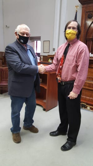 Circuit Court Judge Jay Courrier (right) congratulates Roger Leatherman Friday after administering the oath of office for Leatherman's second term as a Mineral County commissioner.