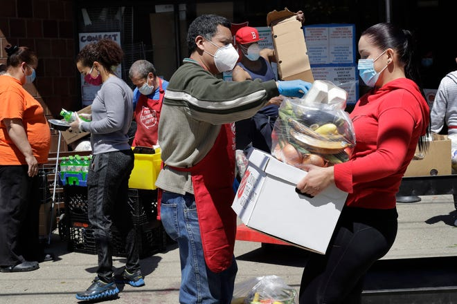 A Salvation Army worker, center, wears a mask and gloves out of concern for the coronavirus while distributing food in May to a person, right, also wearing a mask, in Chelsea.