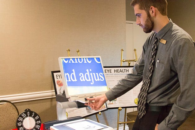 Hunter Duerr, assistive technology instructor, demonstrates a CCTV reader during the Dining in the Dark fundraiser several years ago. The Florida Center for the Blind and many other local groups need volunteers.