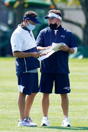 New England Patriots quarterbacks coach Jedd Fisch, left, and offensive coordinator Josh McDaniels, right speak during training camp at Gillette Stadium on Aug. 23, 2020 in Foxborough, Massachusetts. Fisch is leaving to become the next head coach at the University of Arizona.