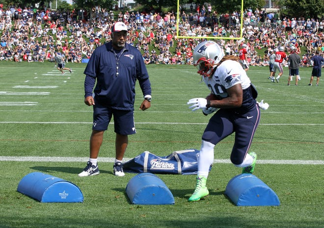 Running back Brandon Bolden runs a drill as Ivan Fears, running back coach watches at New England Patriots 2014 Training Camp on the practice field at Gillette Stadium.