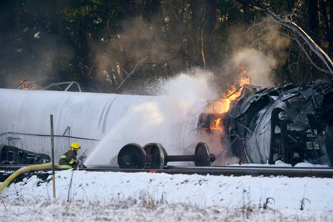 A firefighter sprays foam on a burning, derailed train car Tuesday, Dec. 22, in Custer, Wash. Officials say seven train cars carrying crude oil derailed and five caught fire north of Seattle and close to the Canadian border. Whatcom County officials said the derailment occurred in the downtown Custer area, where streets were closed and evacuations ordered during a large fire response.