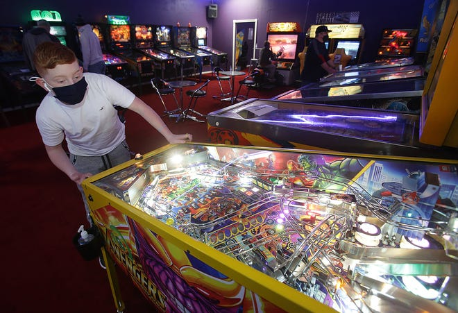 "Carson Presutti, 14, of Perry Township, plays an ""Avengers"" pinball game Monday at Rack it Up Classic Arcade in Jackson Township."