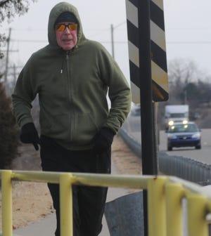 Mike Allen runs on a sidewalk along E. Crawford Street during his 10-mile run on Monday morning. Allen is preparing to run a marathon next year.