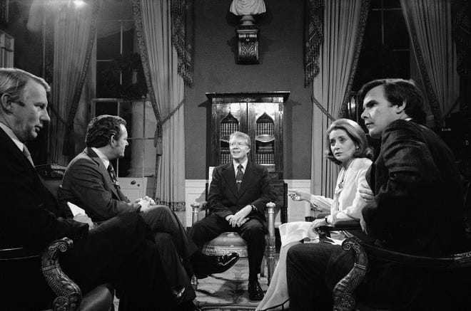 President  Jimmy Carter is interviewed by four television reporters on Wednesday, Dec. 28, 1977, in the Red Room of the White House at Washington. From left, Bob McNeil, PBS; Bob Schieffer, CBS; Carter; Barbara Walters, ABC; and Tom Brokaw, NBC.