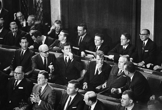 Sen. Edward M. Kennedy, D-Mass., holds a cane as he sits beside his freshman senator brother, Robert Kennedy, D-N.Y., in the last row on the floor of the House chamber for President  Lyndon Johnson's State of the Union speech on Jan. 4, 1965, in Washington. When he was Attorney General, Robert sat in the front row for such speeches.