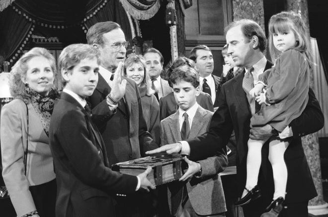 Sen. Joe Biden (D-Del.) holds his daughter Ashley while taking a mock oath of office from Vice President George Bush during a ceremony on Capitol Hill on Jan. 3, 1985. Biden's sons Beau and Hunter hold the bible during the ceremony.