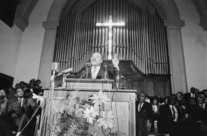 """Dr. Martin Luther King Jr., center, speaks to a wildly cheering crowd of African American supporters Jan. 2, 1965, Selma, Ala. King was calling for a new African American voter registration drive throughout Alabama and promising to """"march on the ballot boxes"""" unless African American are given the right to vote."""