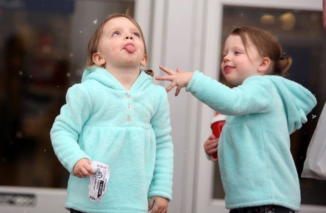 Hannah and Madelyn Turner catch snowflakes while leaving Cleveland Mall in January.