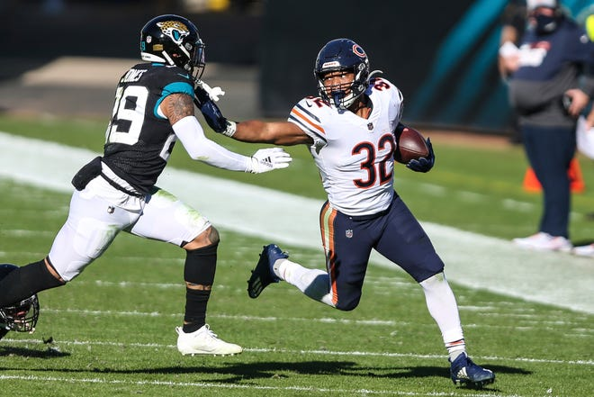 Chicago Bears running back David Montgomery (32) stiff-arms Jacksonville Jaguars safety Josh Jones (29) Sunday. [Gary McCullough/The Associated Press]