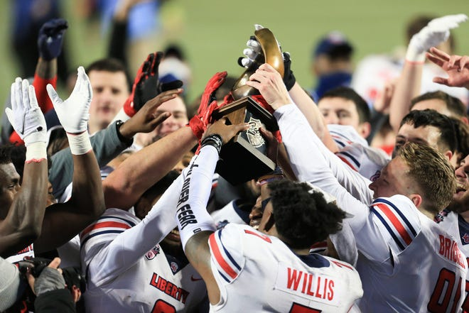 Liberty players celebrate with the trophy after defeating Coastal Carolina in overtime in the Cure Bowl NCAA college football game Saturday, Dec. 26  in Orlando, Fla.