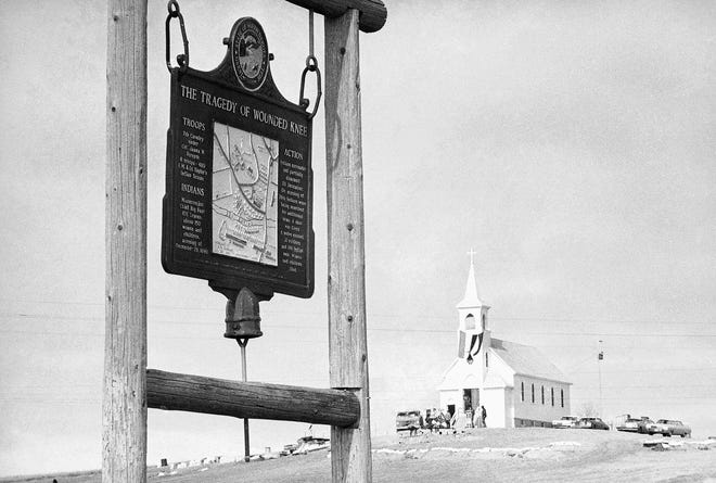 The historical marker commemorating the Wounded Knee Massacre of Dec. 29, 1890, stands on the road near the Sacred Heart Catholic Church.